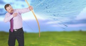 Übendes Bogenschießen des Geschäftsmannes mit grünem Feld herein Stockfotografie