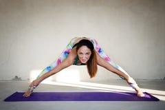 Übendes Yoga der jungen Frau in einem städtischen Hintergrund Lizenzfreies Stockfoto