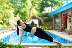 Übendes Yoga des asiatischen Mädchens auf einer Bank Stockbild