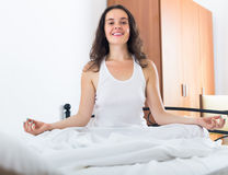 Übendes Yoga des Mädchens im Bett Lizenzfreie Stockfotos