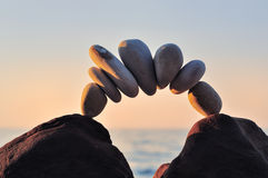 Bending. Arc of pebbles between of the stones on the coast Royalty Free Stock Image