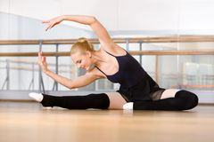 Bending ballerina stretches herself on the floor. Bending ballerina stretches herself on the wooden floor in the classroom Royalty Free Stock Image