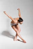 Bending ballerina in studio Stock Images