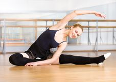 Bending ballet dancer stretches herself on the floor. Bending ballet dancer stretches herself on the wooden floor in the classroom Stock Images