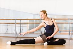 Bending ballet dancer stretches herself on the wooden floor. Bending ballet dancer stretches herself on the floor in the classroom Royalty Free Stock Image