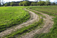 Bending country road. Bend of muddy country road among meadows in spring Stock Photography