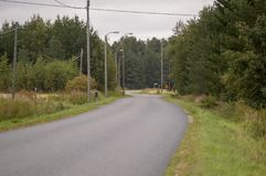 Bending country road. Paved country road with a sign warning about dangerous bend Stock Photo