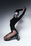 Bending dark woman in rhinestones. In studio Stock Photography