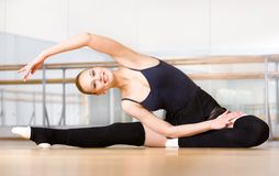 Bending female ballet dancer stretches herself on the wooden floor. Bending female ballet dancer stretches herself on the floor in the classroom Royalty Free Stock Photo