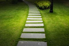 Bending garden stone path at night with glowing light from garden outdoor light.  Stock Photo