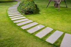 Bending garden stone path at night with glowing light from garden outdoor light.  Royalty Free Stock Photo