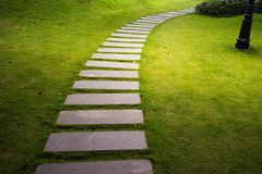 Bending garden stone path at night with glowing light from garden outdoor light.  Royalty Free Stock Photography