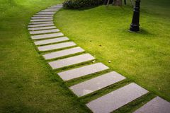 Bending garden stone path at night with glowing light from garden outdoor light.  Stock Image