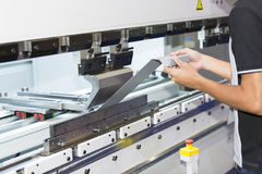 Bending metal sheet by sheet bending machine. Operator bending metal sheet by sheet bending machine Royalty Free Stock Photography