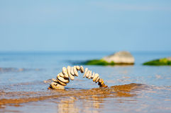 Bending pebbles. Circle of pebbles on the surface of the sea Royalty Free Stock Photo