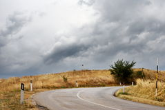 Bending road in countryside. Scenic view of bending road in countryside with dark cloudscape background royalty free stock photo