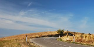 Bending road on hillside. Wide angle view of bending or curving road on hillside with blue sky and cloudscape background stock photo