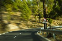 Bending road (moving effect/traffic sign). A bending road in the mountains of Tenerife, Spain Royalty Free Stock Photography