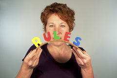 Bending the Rules. Mature woman concentrating at the word RULES while she is bending it Stock Photos