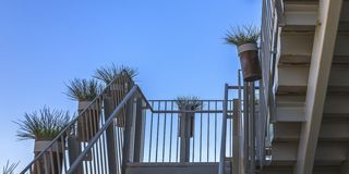 Bending stairs with potted plants on the handrail. View of a white bending stairs against a clear bue sky. Potted green plants line the handrails of the metal stock photo