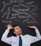 Bending under stack of problems. Businessman bending under stack of problems Stock Photo