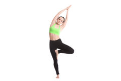 Bending in vrikshasana yoga pose. Sporty girl on white background doing fitness workout for spine, side bending in Tree Pose, asana vrikshasana, Vriksasana, yoga Stock Photo