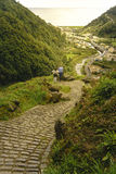 Bending yellow stone pavement pathway descending to the river. Adult couple standing and looking for the sun rays over a tiny vill stock image