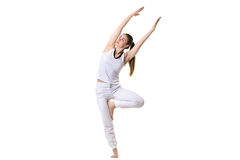 Bending in Yoga tree pose. Full length portrait of young fitness model in white sportswear doing yoga or pilates training, side bending in Tree Pose, asana Stock Photography