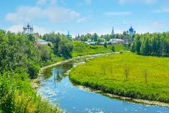 The bends of Kamenka river in Suzdal. The bend of Kamenka river in historic center of Suzdal, the domes of Kremlin`s Nativity Cathedral, Assumption church and Royalty Free Stock Photography
