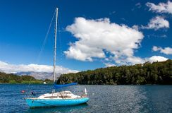 Beneath blue sky. Sailing boat in lake Manapouri New Zealand Royalty Free Stock Image