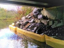 Riprap containment from yellow plastic floating boom. Beneath a bridge under repair in the Adirondacks during October 2018, solid floats barricade the motionless royalty free stock photo