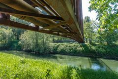 Beneath The Bridge 2. A view from beneath a rusty metal walking bridge that spans the Green River in Kent, Washington Royalty Free Stock Photo