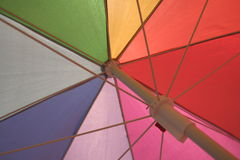 Beneath a brightly colored umbrella. Protecting us from the glare of the sun Stock Image