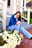Beneath my Gaze. Young female teen sits on steps of home and stares intensely.  Lips pursed and a steely gaze pins you down Royalty Free Stock Photos