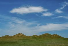Beneath the Summer Sky of Nebraska. A series of interesting hills break up the otherwise flat prairies of western Nebraska beneath a beautiful summer sky Stock Photos