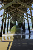Beneath Sunset Beach Pier. A view of the Atlantic Ocean from Beneath Sunset Beach Pier in NC stock image