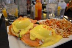 Benedict Eggs con il salmone e le patate fritte Immagine Stock