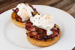 Benedict eggs with crispy bacon and hollandaise sauce on toasted Maffin. On clean plate Royalty Free Stock Images
