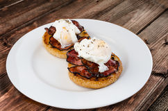Benedict eggs with crispy bacon and hollandaise sauce on toasted Maffin. On clean plate Royalty Free Stock Photo