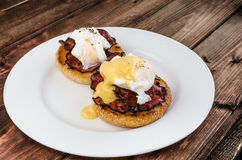 Benedict eggs with crispy bacon and hollandaise sauce on toasted Maffin. On clean plate Royalty Free Stock Image