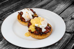 Benedict eggs with crispy bacon and hollandaise sauce on toasted Maffin. On clean plate Royalty Free Stock Photos
