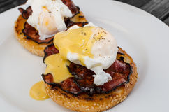 Benedict eggs with crispy bacon and hollandaise sauce on toasted Maffin. On clean plate Stock Photo