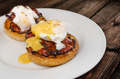 Benedict eggs with crispy bacon and hollandaise sauce on toasted Maffin Royalty Free Stock Image