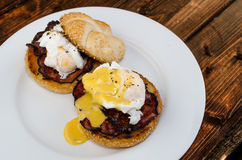 Benedict eggs with crispy bacon and hollandaise sauce on toasted Maffin Royalty Free Stock Images