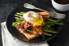 Benedict ha affogato l'uovo dell'anatra con bacon croccante ed asparago fritto sui pani tostati per la prima colazione fotografia stock libera da diritti