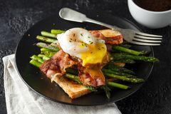 Benedict poached Duck egg with crispy bacon and fried asparagus on toasts for breakfast royalty free stock photography