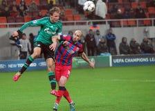 Benedikt Höwedes e Iasmin Latovlevici durante juego de la liga de campeones de UEFA Imagenes de archivo