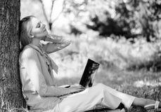 Benefici di aria aperta del lavoro Donna con del computer portatile del lavoro l'albero magro all'aperto Il minuto per si rilassa fotografia stock