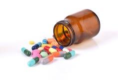 Beneficiario de la medicina y muchas píldoras aisladas en el backgroun blanco Fotos de archivo libres de regalías