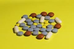 Beneficiario de la medicina y muchas píldoras aisladas en el fondo amarillo, concepto de salud imagen de archivo